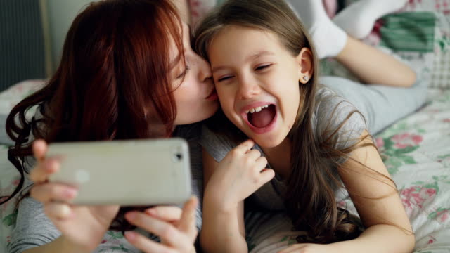 Closeup of Happy mother and little girl taking selfie photo with smartphone camera and have fun grimacing while sitting in cozy bed at home. Family, people and technology concept