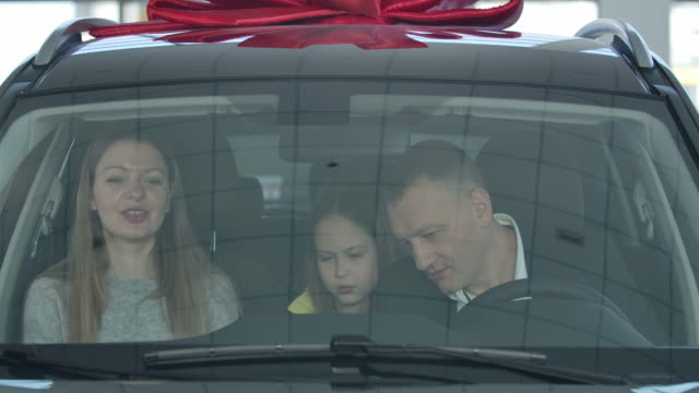 Close-up of happy successful Caucasian family buying vehicle in dealership. Shooting through windowsill of three people talking and smiling in automobile in showroom. Cinema 4k ProRes HQ.