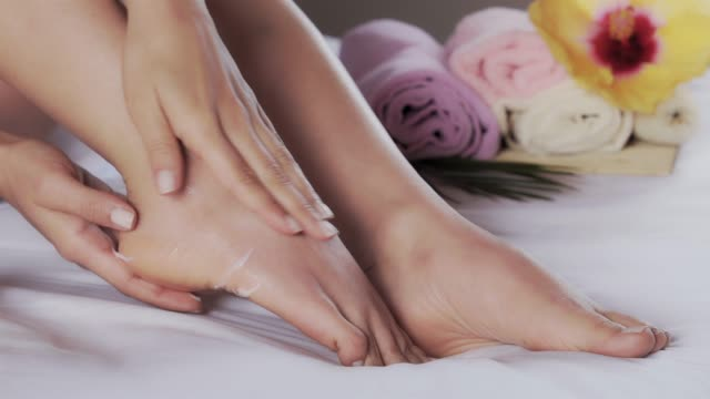 vídeos de stock e filmes b-roll de close-up of hispanic young woman applying moisturizing cream on her feet after taking a bath - feet hand