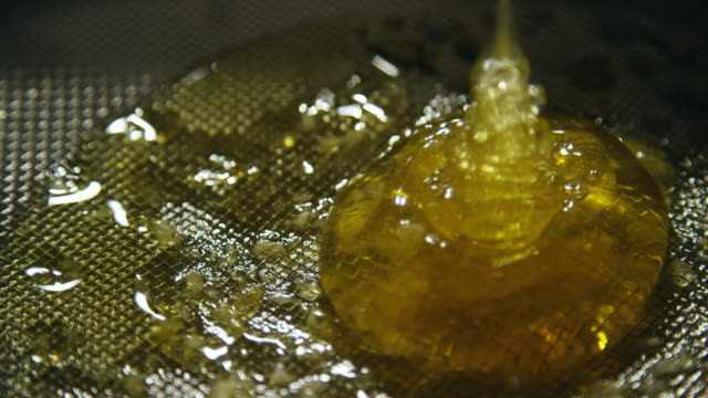 Close-Up of Honey Pouring onto a Metal Sieve