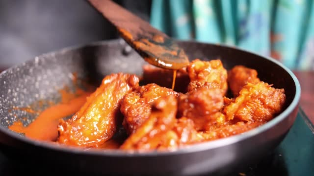 Closeup of hot and spicy buffalo chicken wings being stirred in a non-stick pan Closeup of hot and spicy buffalo chicken wings being stirred in a non-stick pan spice stock videos & royalty-free footage
