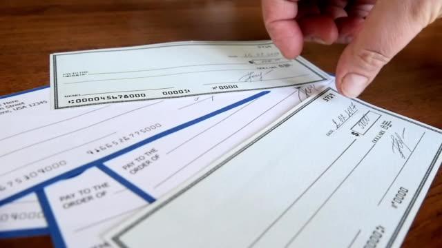 vídeos y material grabado en eventos de stock de primer plano de la mano humana llenar cheque - accesorio financiero