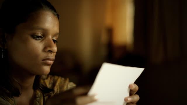 vídeos de stock e filmes b-roll de close-up da menina indiana a sorrir ao ler a carta - mensagem