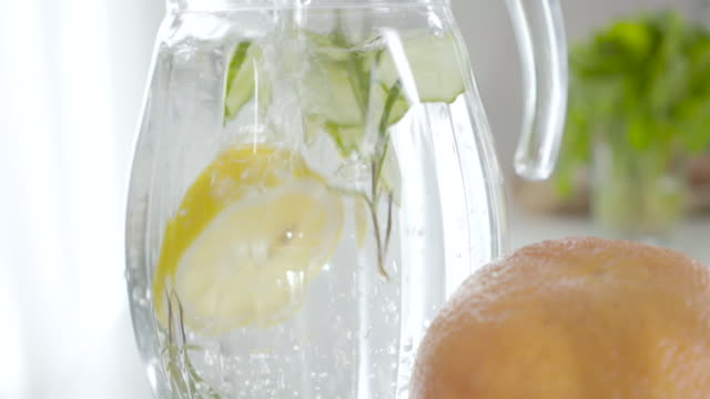 close-up of infused herbal detox cocktail in transparent pitcher. slowmo of water pouring into glass container with herb, sliced cucumber and lemon. hydration, nutrition, wellbeing, healthy lifestyle. - большой кувшин стоковые видео и кадры b-roll