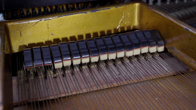 Closeup of Inside classic piano hammers strikes the strings.
