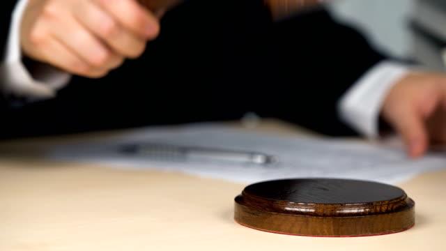 nahaufnahme des richters hände auffällig hammer im gerichtssaal, verfahren beginnen oder enden - dominanz stock-videos und b-roll-filmmaterial