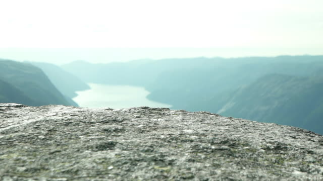 closeup of kjeragbolten's surface and a panoramic view of rivers and mountains - fiordo video stock e b–roll