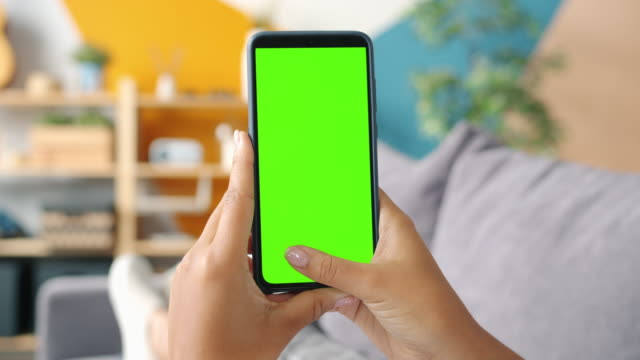 Close-up of lady's hands holding smartphone with mock-up green screen swiping