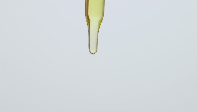 close-up of lavender oil drops falling from the pipette, on the white background. the pipette is held vertically. - goccia video stock e b–roll
