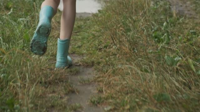 vídeos de stock, filmes e b-roll de close-up dos pés nas botas da menina que funciona na poça de chuva do verão na estrada secundária - alto descrição geral