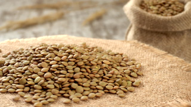Close-up of lentil rotating on burlap. Rustic wooden background. Seamless loopable video