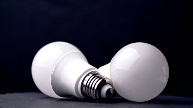 nahaufnahme der glühbirnen auf dem tisch - led leuchtmittel stock-videos und b-roll-filmmaterial