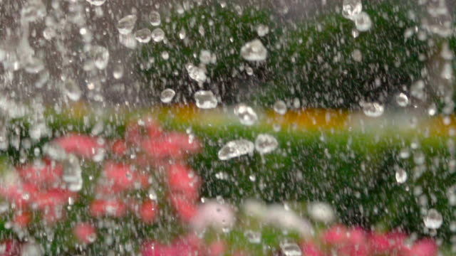 Closeup of light splashing water in sunny fountain in park in summer. Water fountain in garden. Super slow motion.