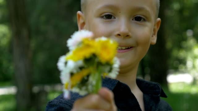Nahaufnahme des kleines Kind halten und geben einen Blumenstrauß und bieten Ihnen – Video