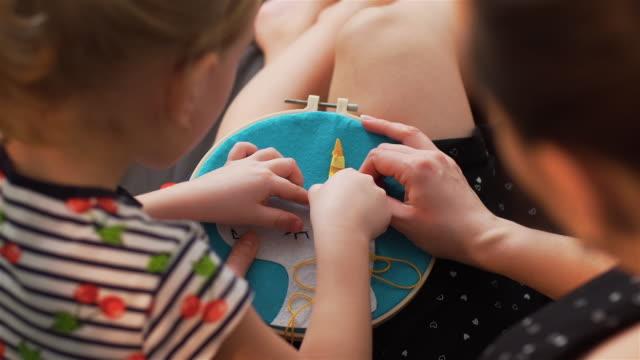 vidéos et rushes de le plan rapproché de la petite fille est engagé dans la couture - artisanat