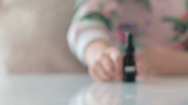 Close-up of Little Girl Pushing CBD Oil Drops Container in Focus Close-up of Little Girl Pushing CBD Oil Drops Container in Focus. cbd oil stock videos & royalty-free footage