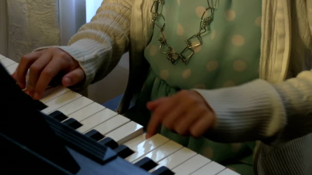 Closeup of little girls hands playing piano in blue dress video