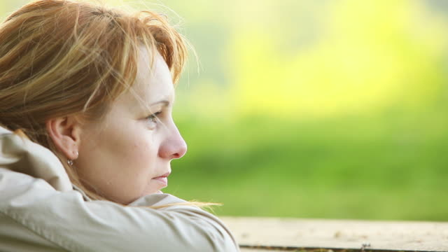 Close-up of lonely young woman in the park Full HD: Close-up shot of young woman's face. Woman leaning on a park bench looking in front of her in deep thoughts. park bench stock videos & royalty-free footage