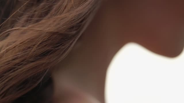 close-up of long brown curly hair and naked shoulder of young woman in windy day - lungo video stock e b–roll