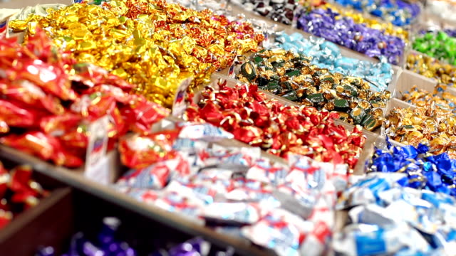 Close-up of lots of candy in colorful wrappers in a pastry shop. Large choice of sweets in a candy shop. Close-up of lots of candy in colorful wrappers in a pastry shop. Supermarket. candy stock videos & royalty-free footage