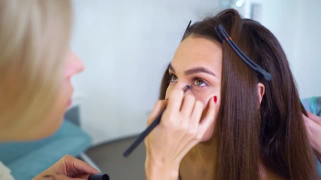 closeup of makeup artist applying eyeshadows with brush on young woman's face at beauty salon - femminilità video stock e b–roll