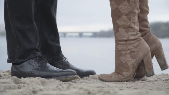 Close-up of male and female feet standing on sand on riverbank. Unrecognizable woman raising one leg in elegant brown boot. Confident couple dating outdoors. Romance, love, leisure, lifestyle