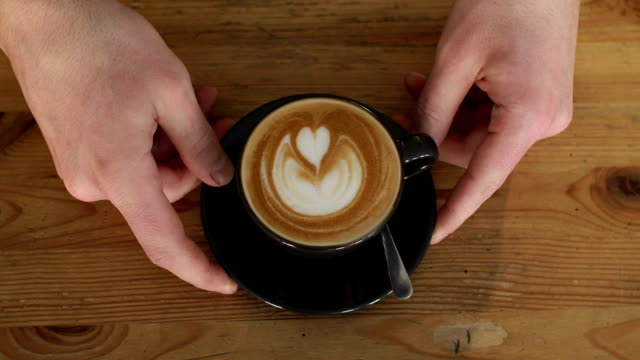 Close-up of male Barista puts a latte Cup with a heart on the foam on the table.