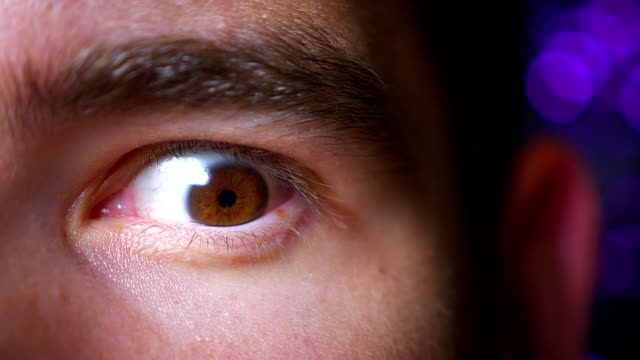 närbild av manliga bruna vidöppna öga i ett upphetsad tillstånd tittar rakt på kameran på bakgrunden ogf natt lampor - male eyes bildbanksvideor och videomaterial från bakom kulisserna