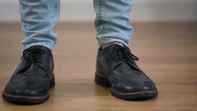 Close-up of male Caucasian feet in elegant broggi shoes stomping on the floor. Adult man jumping down, turning and leaving to the right. Close-up of male Caucasian feet in elegant broggi shoes stomping on the floor. Adult man jumping down, turning and leaving to the right. stamping feet stock videos & royalty-free footage
