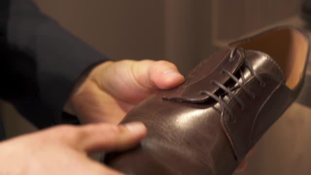 購入する前に茶色の革の靴を見ている男性のクライアントのクローズアップ。様々な選択肢があります。ショップと販売のコンセプト。 - 靴点の映像素材/bロール