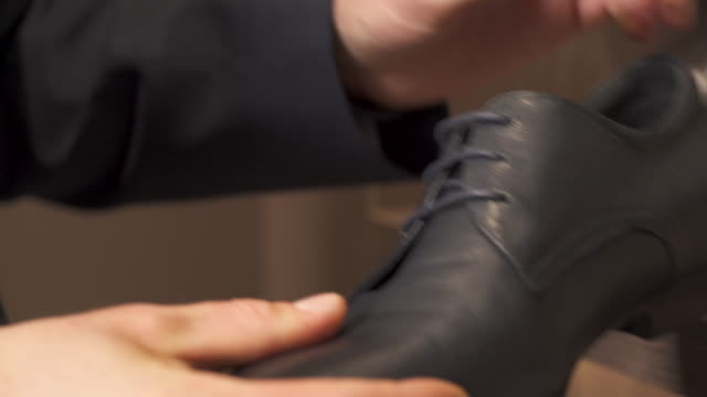 A close-up of male customer checking a quality of black leather shoes before buying. Shop and sale concept.