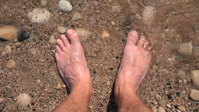 Close-up of male feet on the beach. The waves and sand. video