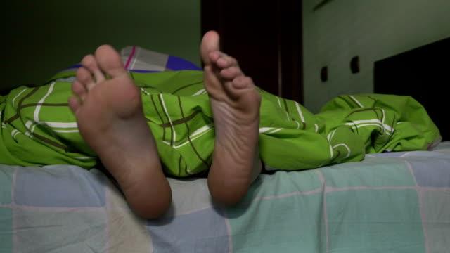 närbild av manliga fötter spela i sängen - duntäcke bildbanksvideor och videomaterial från bakom kulisserna