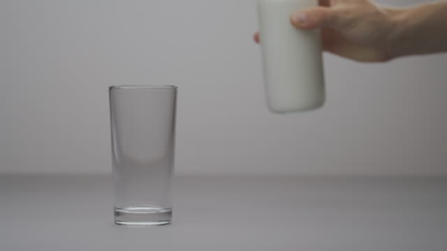 Close-up of male hand holding jar and pouring milk into glass. Healthy nutrition, dairy product. Selective focus shot