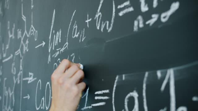 närbild av manliga handskrivande matematiska ekvationer på tavlan i klassen - fysik bildbanksvideor och videomaterial från bakom kulisserna