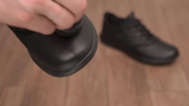 前面に黒い革の靴を保持し、清掃する男性の手のクローズアップ。ぼやけた背景にカジュアルなスタイルのクリーンシューズ。 - 靴点の映像素材/bロール