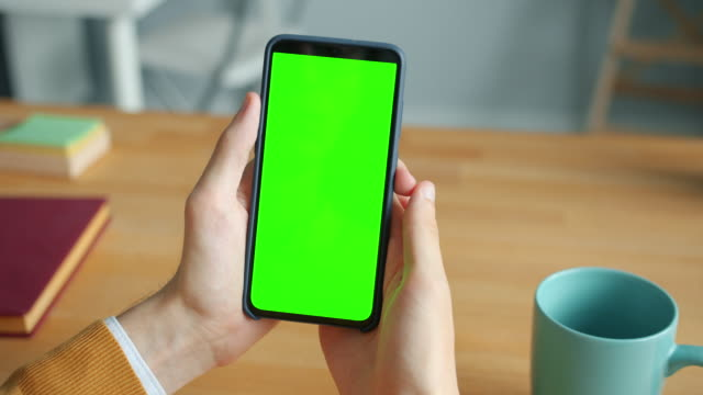 vídeos de stock e filmes b-roll de close-up of male hands holding chroma key green screen smartphone in office - segurar