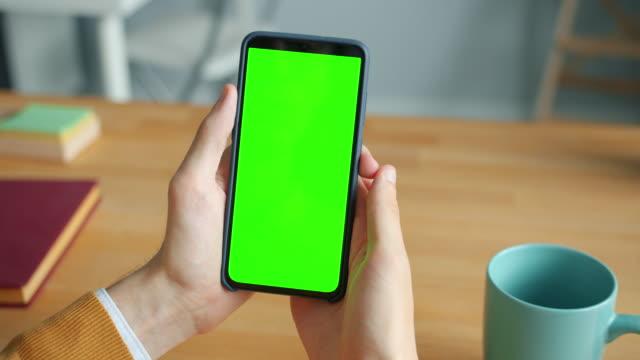 男性手拿著色度鍵綠屏智慧手機在辦公室特寫 - 握住 個影片檔及 b 捲影像