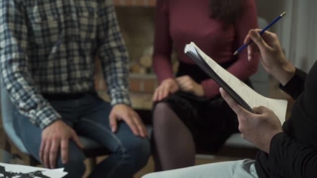 stockvideo's en b-roll-footage met close-up van mannelijke handen vasthouden van papieren en gesturing. jonge blanke man en vrouw die handen op de achtergrond houden. familie of stel nieuws krijgen bij psycholoog of dokters kantoor. - alternatieve therapie