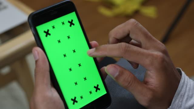 närbild av manliga händer som håller smart telefon med grön skärm - skrollning bildbanksvideor och videomaterial från bakom kulisserna