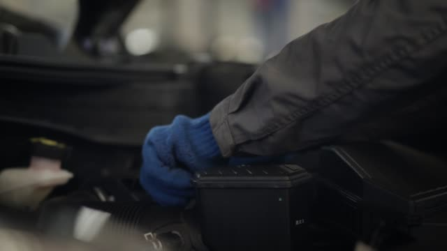 Close-up of male hands in protective gloves taking off engine air filter and putting it back into car bonnet. Professional auto mechanic inspecting vehicle in repair shop. Insurance, tuning, industry.