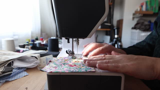 Close-up of male hands sowing a pocket piece with a sewing machine in profile in a home atelier
