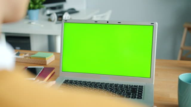 Close-up of male hands using green screen chroma key laptop typing in office
