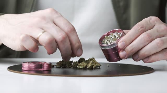 vídeos y material grabado en eventos de stock de primer plano de manos masculinas usando molinillo con cogollos de marihuana medicinal - grind