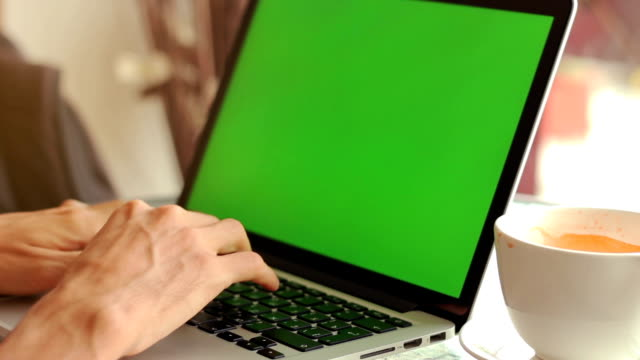 Close-up of male hands using laptop at cafe with green screen video