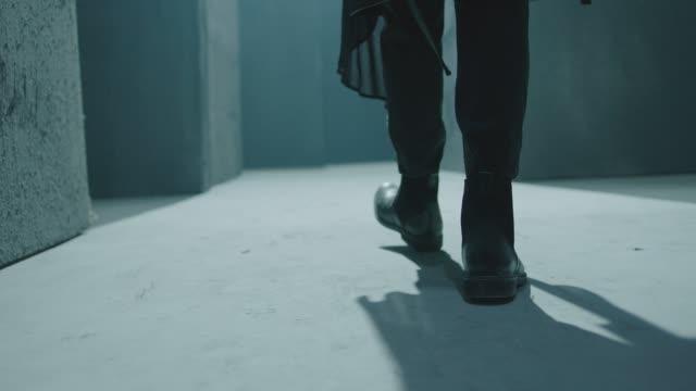 Closeup of male legs in black boots. Rear back view of man walking inside dark maze. Man walking inside dark room, corridor. Footage of mystical video. Shot on ARRI ALEXA Cinema Camera in slow motion