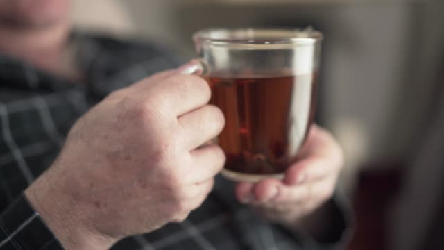 Close-up of male senior Caucasian hands holding cup of tea. Unrecognizable pensioner waving to someone away. Lifestyle of positive retiree, leisure, aging