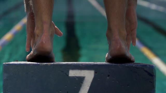 vidéos et rushes de gros plan d'un homme natation sauter de starting block - starting block
