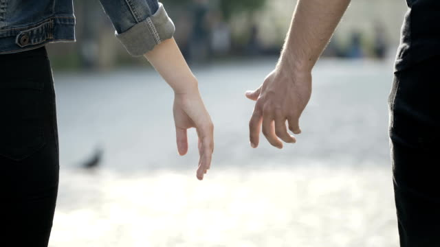Closeup of man and woman touching hands and enjoying a walk together in a park video