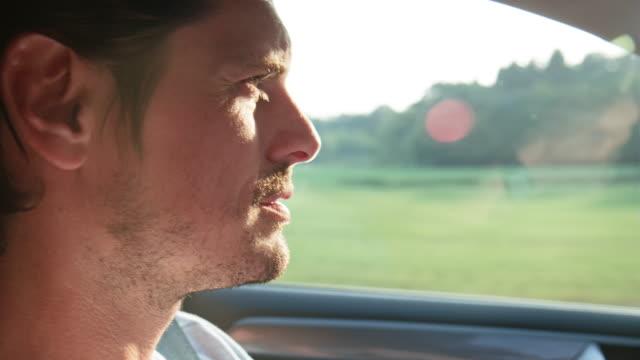 vidéos et rushes de plan rapproché de la voiture de conduite d'homme pendant le voyage de route - conduire